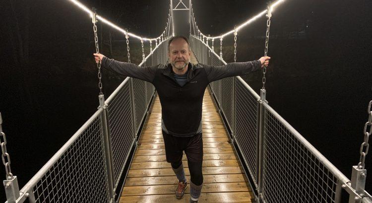 Hängbron över Lagan är upplyst i natten, en man står på den med armarna utsträckta.